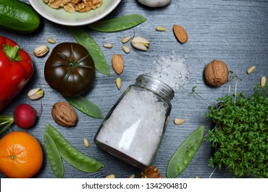 Top view:a glass jar with spilled salt lying on a black surface,a tomato,a pepper,a tangerine, a radish,a cucumber,a garlic,Cress, walnuts,pine nuts,pistachios,almonds,a pea pods & a bowl with walnuts