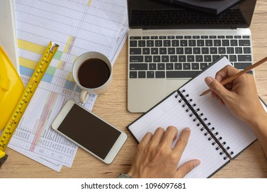 Top view,Business man hand writing content or somethings on notebook with using laptop at wooden table in site office , lifestyle concept