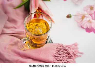 Top view,Cup of medicinal chamomile tea on silky scarf with blurry background of white paper with retro filter,Autumn flat lay with a cup of hot tea and pink flower with copy space, Cozy home concept