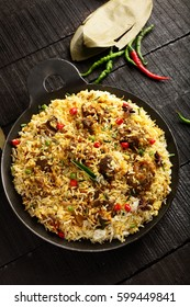 Top view-Delicious homemade mutton or lamb dum biriyani over wooden background,