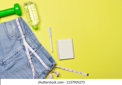 Top view,flat lay an old blue jean style with measuring,dumbbell,notebook,bottle,water on pastel in yellow background it for diet,healthy concept.