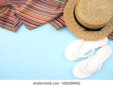Top view,Flat lay sandals beach concept.Craft hat and multi color scarf on indigo blue pastel background with copy space,blank for text.Hipster vacation,Day off holiday traval theme.