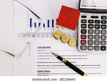 Top views of close up fountain pen and calculator and paper house and coins  and eyeglasses on Loans request form for mortgage loans concept
