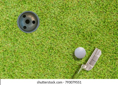 Top views of golf ball putter and golf hole on green grass .with space for text.