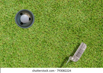 Top views of golf ball and putter and hole on green grass .hole in one concept.with space for text.
