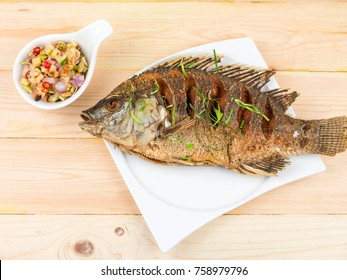 Top View.Thai food deep fried Tilapia fish on white plate with sauce spicy toppings on wooden background.