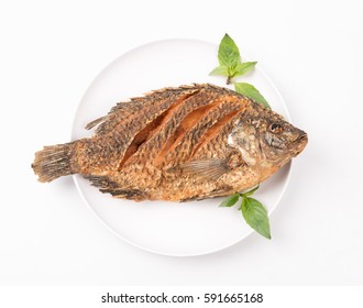 Top view,Tilapia fish fried with basil on white plate isolated over white...