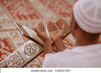 Top viewv of African Muslim Man Making Traditional Prayer To God While Wearing A Traditional Cap Dishdasha