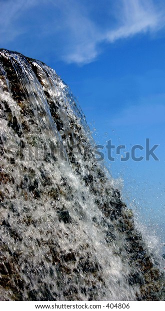The top of a waterfall against a beautiful blue sky