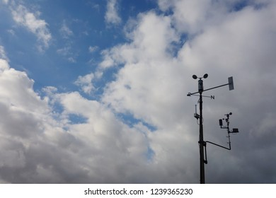Top of weather station on windy cloudy day. Anemometer on right side of frame, under thick cloudy sky. Space to add text & message on fluffy white clouds and blue sky in background.