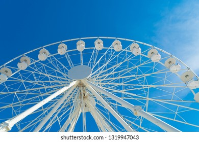 top of a white ferris wheel against a sunny blue sky