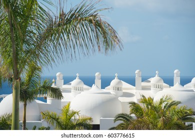 Top of white holiday houses and palm trees on sunny day