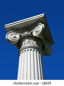 Top of white pillar against sky.