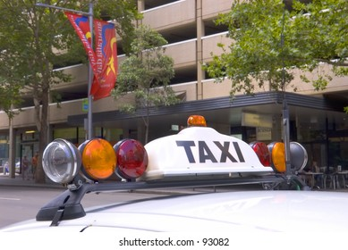 """Top of white taxi showing sign """"TAXI"""""""