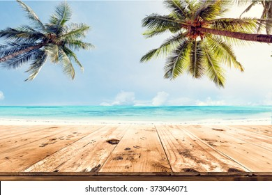 Top of wood table with blurred sea and coconut tree background - Empty ready for your product display montage. Concept of beach in summer