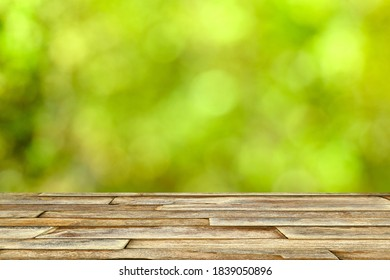 Top wood table on blurred green bokeh background in the park. Copy space. Can be use for advertising to show your product display montage.