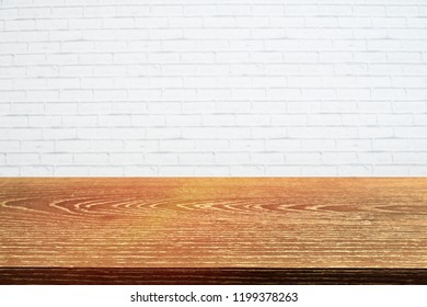 Top wood table on white brick wall background. Mock up for display or montage. Can be use for banner, advertising, Free space for any text or product.