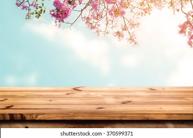 Top of wood table with pink cherry blossom flower on sky background - Empty ready for your product display or montage.