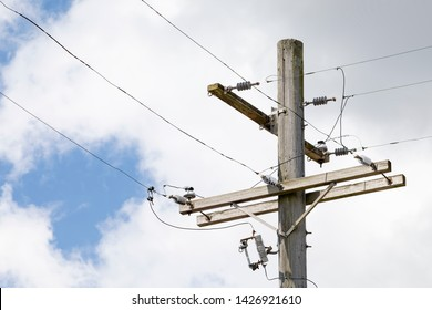 Top of a Wood Utility Pole with Lines against a Cloudy Blue Sky