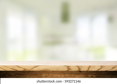 Top wooden table and in the blurry background interior of the kitchen with windows. Empty space to paste and mounting of different products.