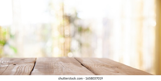 Top of wooden table on window glass blur. Of green from the garden of the vegetable garden on a morning background. To display product montage.