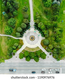 Top-down aerial photo of a park with a circular paved area with sidewalks coming out of it surrounded by trees as well as a road with vehicles on it