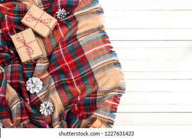Top-down Christmas composition with plaid, gift boxes, cones and copy space on white wooden background.