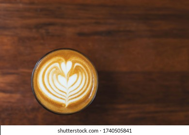 Top-down hot latte coffee cup on wooden tabel with copy space for text.
