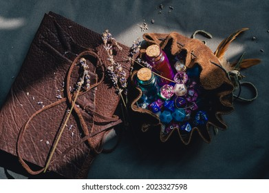 Top-down image of a leather-bound notebook, a brown-leather dice bag with RPG-dice, and two potion bottles in a ray of sunlight