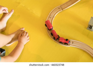 top-down shot of a young girl playing with wooden toy train on a yellow playroom floor