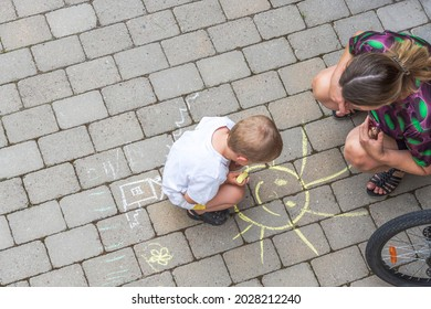 Top-down view on child drawing on paving slabs and woman watching him. Sweden. Uppsala. 08.20.2021.