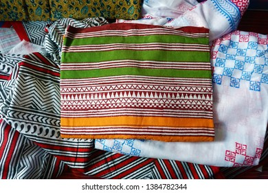 Top-down view of traditional kalamkari cotton sarees displayed for the customers to choose, in a textile shop.