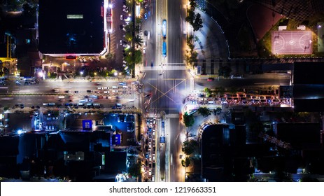 Top-down view of traffic jam on road junction with crosswalk at night time in Jakarta city