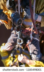 Tope view of female rope access worker hand wearing safety glove using descender commencing abseiling descending with casualty during rescue operation construction site Sydney, Australia