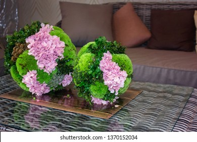 Topiary of pink flowers and evegreen plants. Topiary balls. Floral Topiary design. Rattan furniture.