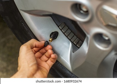 Topic of problems with the car. hand placing tire valve cap on car tire. car repairs at home