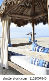 topical outdoor beach bed palapa palm thatched roof glamping in Baja, Mexico