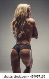 Topless blond female in black panties from the back.