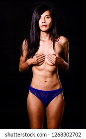Topless Chinese woman with hand on breasts