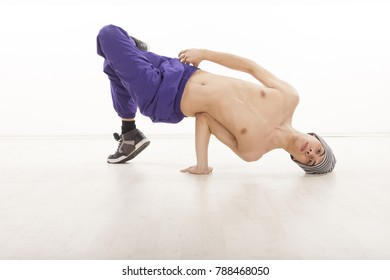 Topless dancer in breakdance postion wearing ultraviolet pants, sitting on one hand and hand on the wood floor. Studio image on white background.