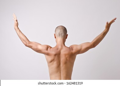 Topless dancer, man stripper posing with his back and arms up opened. Fit bodybuilder.