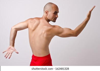 Topless dancer, man stripper posing with his back and arm up. Fit bodybuilder.
