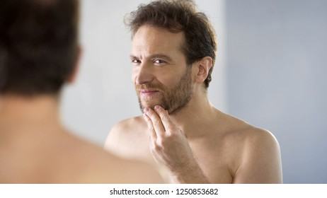 Topless male critically looking at his beard in mirror, morning ritual, bathroom