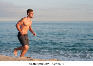 Topless man Barefoot Running on beach