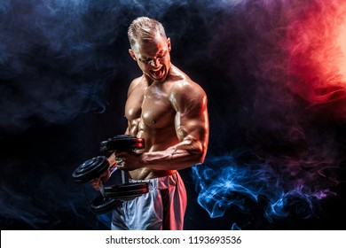 Topless man exercising biceps with dumbbells posing in studio fuul of colored smoke