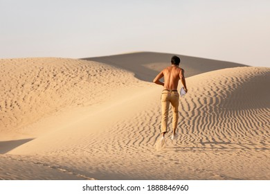 Topless Man running  in a desert at sunrise