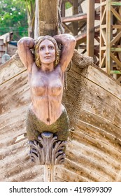 Topless mermaid on bow of boat.