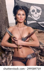 Topless pirate woman covers her breasts with a classic pistols
