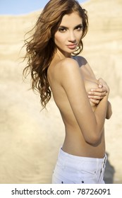 topless sensuality brunette girl in white  jeans over sand background