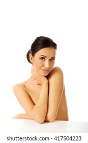 Topless woman sitting and looking at the camera